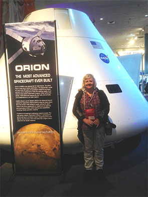 Wendy Shearer standing in front of a rocket and banner describing Orion, the most advanced spacecraft ever built
